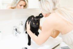 Blonde Frau, die mit schwarzer Katze im Badezimmer auf Waschbecken - reizendes Haustier spielt stockfotografie