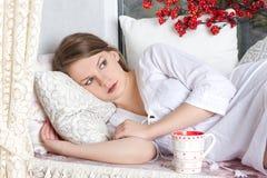 Blonde Frau, die mit Tasse Kaffee am Schlafzimmer aufwacht Stockfotografie