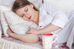 Blonde Frau, die mit Tasse Kaffee am Schlafzimmer aufwacht Lizenzfreie Stockfotografie