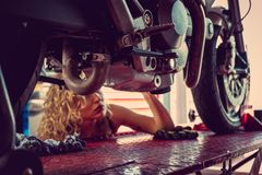 Blonde Frau, die Motorrad repariert Lizenzfreie Stockfotos