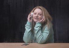 Blonde Frau, die Musik, schauend aus einem Fenster heraus hört Lizenzfreie Stockfotografie