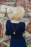 Blonde Frau, die nahe dem Bild mit gemaltem Graphit steht Stockfotografie
