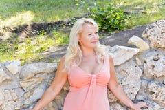 Blonde Frau, die nahe dem Felsen steht Lizenzfreie Stockfotos