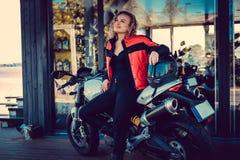 Blonde Frau, die nahe Motorrad aufwirft Lizenzfreie Stockbilder