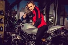 Blonde Frau, die nahe Motorrad aufwirft Lizenzfreie Stockfotografie