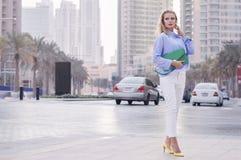 Blonde Frau, die nahe verkehrsreicher Straße mit Autos in Dubai im Stadtzentrum gelegen steht Stockbilder