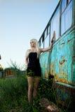 Blonde Frau, die nahe verlassenem Bus steht Stockfotografie