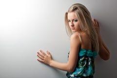 Blonde Frau, die nahe Wand aufwirft Lizenzfreies Stockbild
