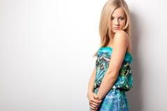 Blonde Frau, die nahe Wand aufwirft Lizenzfreie Stockfotografie