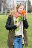 Blonde Frau, die orange Tulpen hält Lizenzfreie Stockbilder