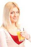Blonde Frau, die Orangensaft trinkt Lizenzfreie Stockfotografie