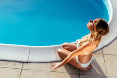 Blonde Frau, die am Pool meditiert Lizenzfreies Stockfoto