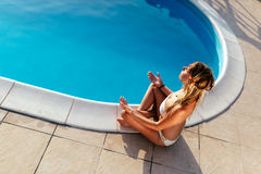 Blonde Frau, die am Pool meditiert Stockbild