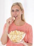 Blonde Frau, die Popcorn isst Lizenzfreies Stockbild