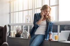Blonde Frau, die pro Handy nahe Fenster spricht Lizenzfreie Stockbilder