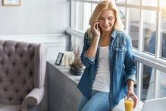 Blonde Frau, die pro Handy nahe Fenster spricht Lizenzfreies Stockfoto