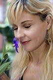 Blonde Frau, die purpurrote Blume mit ihren Augen clos riecht Lizenzfreie Stockbilder