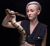 Blonde Frau, die Pythonschlange hält Stockfotos