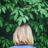 Blonde Frau, die rückwärts neben den Bäumen steht Lizenzfreie Stockbilder