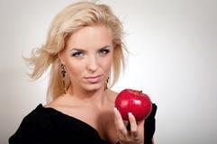 Blonde Frau, die roten Apfel anhält Stockfoto