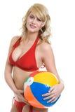 Blonde Frau, die roten Bikiniholding-Wasserball trägt Stockfotografie