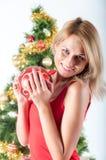 Blonde Frau, die roten Weihnachtsball hält Lizenzfreies Stockbild