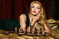 Blonde Frau, die Schach spielt Lizenzfreies Stockfoto