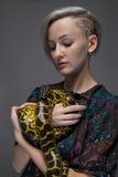 Blonde Frau, die Schlange hält Stockfotografie