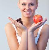 Blonde Frau, die Schokolade und Apfel zeigt Stockfoto
