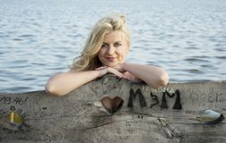 Blonde Frau, die am See aufwirft Stockfoto