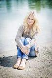 Blonde Frau, die am See sitzt Lizenzfreies Stockbild