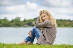 Blonde Frau, die am See sitzt Lizenzfreie Stockbilder