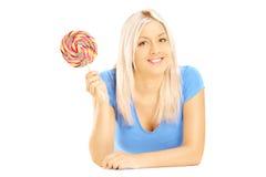 Blonde Frau, die sich mit Lutscher hinlegt und Kamera betrachtet Lizenzfreies Stockfoto