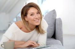 Blonde Frau, die Tablette auf Sofa verwendet Stockfotos
