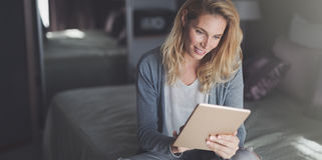 Blonde Frau, die Tablette verwendet Stockbild
