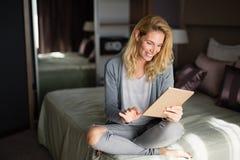 Blonde Frau, die Tablette verwendet Stockfoto