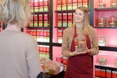 Blonde Frau, die Tee im organischen Shop wählt Stockbilder