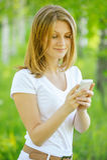 Blonde Frau, die Telefon betrachtet Stockfotografie