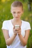 Blonde Frau, die Telefon betrachtet Lizenzfreies Stockfoto