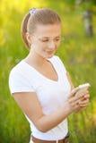 Blonde Frau, die Telefon betrachtet Lizenzfreie Stockbilder