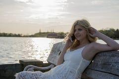 Blonde Frau, die am Telefon durch den See spricht Lizenzfreie Stockbilder