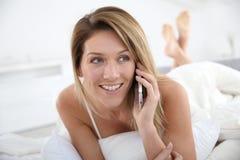 Blonde Frau, die am Telefon liegt im Bett spricht Lizenzfreie Stockfotografie