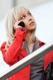 Blonde Frau, die um das Telefon ersucht Stockfotos