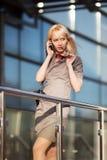 Blonde Frau, die um das Telefon ersucht Lizenzfreie Stockfotografie