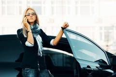 Blonde Frau, die um das Telefon ersucht Stockfotografie