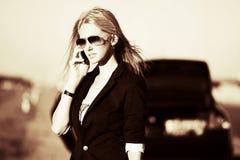 Blonde Frau, die um den Handy ersucht Stockbild