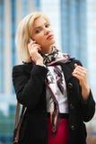 Blonde Frau, die um den Handy ersucht Stockfotos