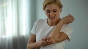 Blonde Frau, die unter den Ellbogenschmerz, ihren schmerzenden Arm, Verletzung und Klammer halten leidet stockfoto