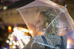 Blonde Frau, die unter ihrem Regenschirm in Deckung geht Stockfotos