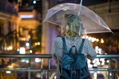 Blonde Frau, die unter ihrem Regenschirm in Deckung geht Stockbild